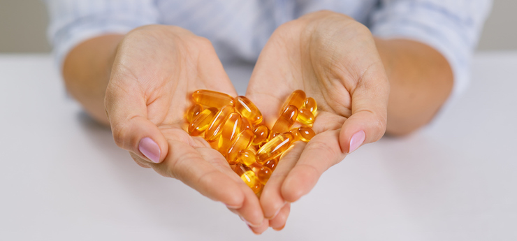 Hands of a woman holding fish oil Omega-3 capsules.