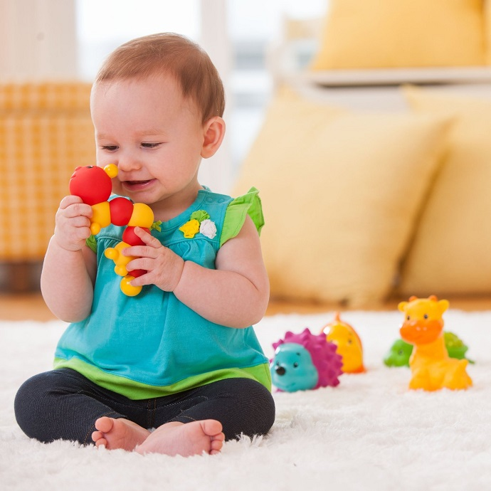picture of a baby playing with a toy on the carpet