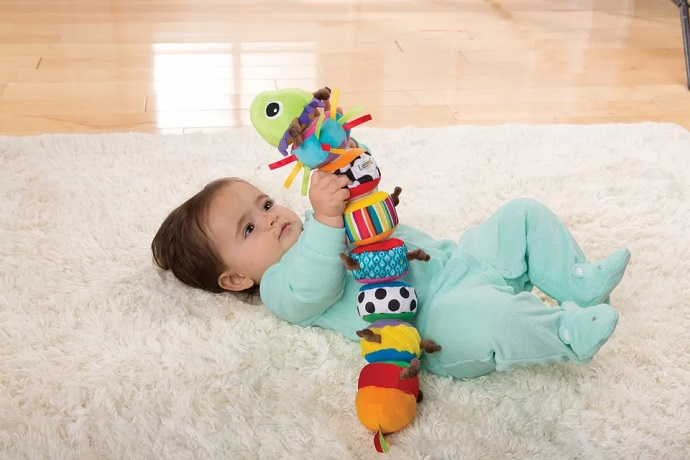 picture of a baby playing with a toy lying on the floor on a soft carpet
