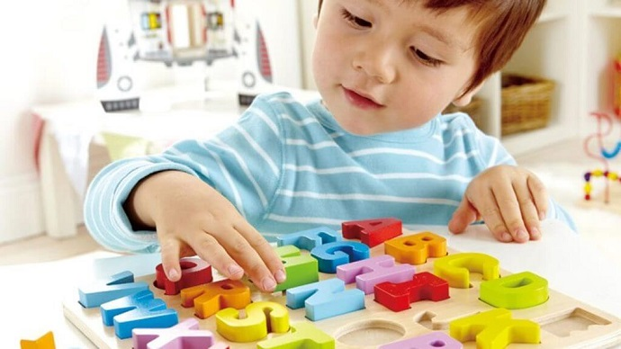 picture of a baby boy playing with letters and numbers