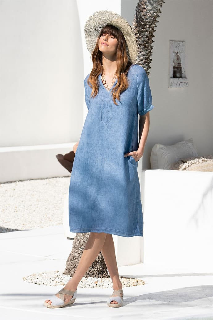 girl with blue linen summer dress and hat on her head