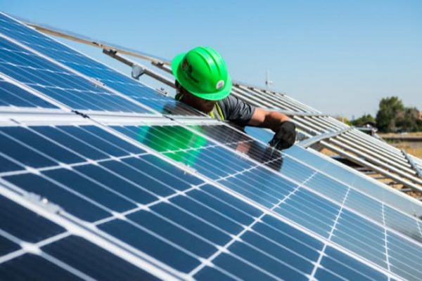 man working on a solar panel monitoring system