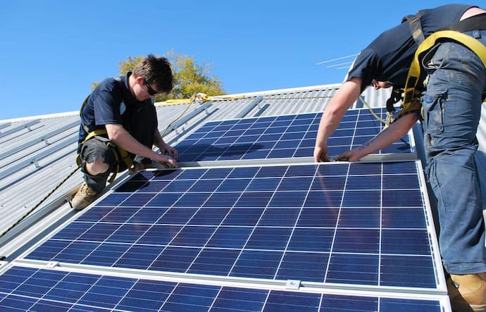 two men installing solar power system on the rooftop