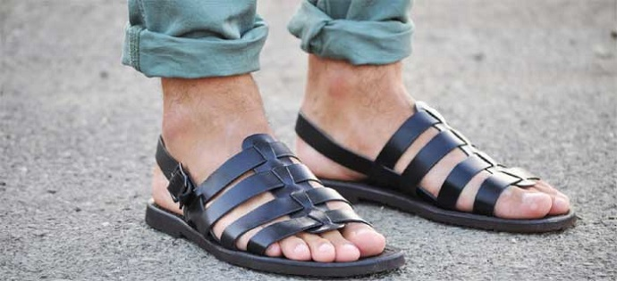 picture of a man's feet in black gladiator sandals and blue pants