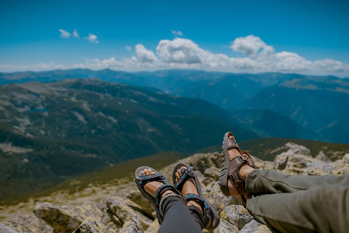 picture of two persons on a mountain sitting on the rocks, wearing pants and sandals