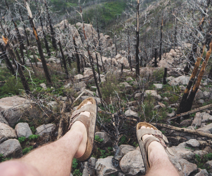 picture of person sitting on a cliff with a view of rocks and threes wearing brown cork slip-on sandals