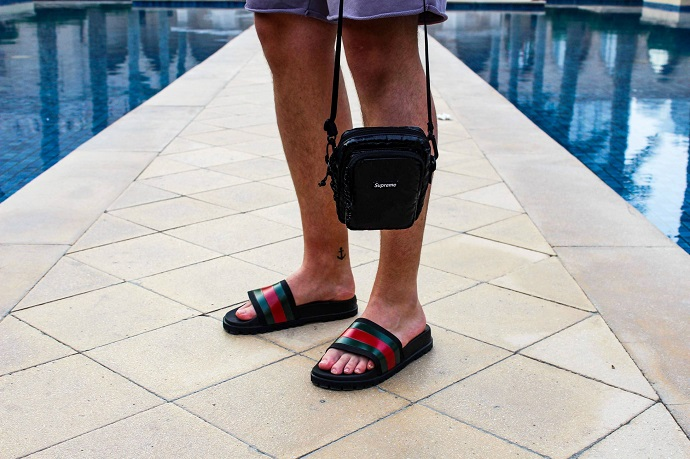 picture of a man walking on tiles beside fountain wearing shorts and sandals