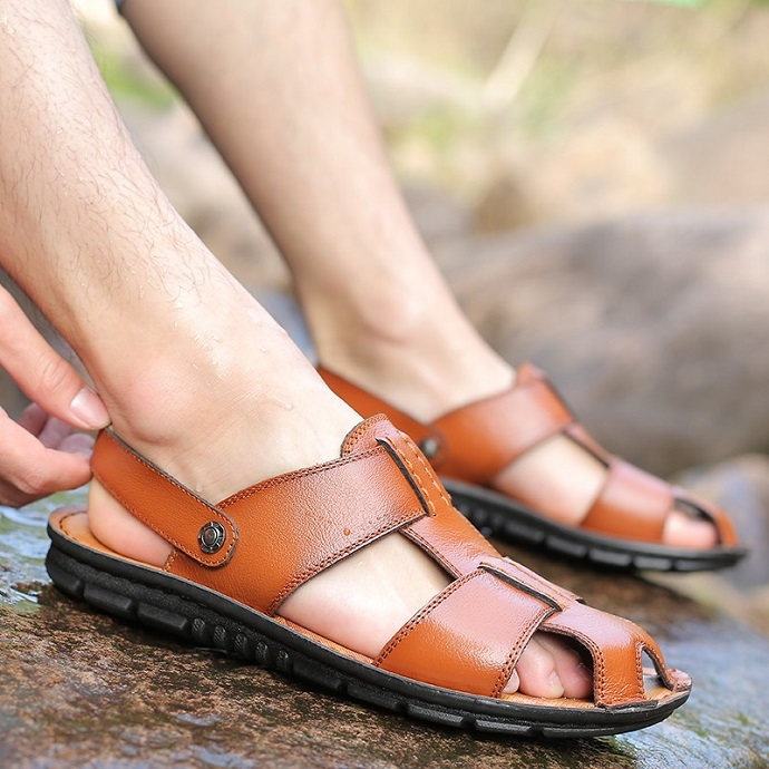 picture of person wearing brown leather sandals on a wet rock