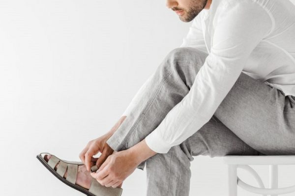 picture of a man wearing white shirt and gray pants, putting on a gray sandals on his feet, sitting on a white chair