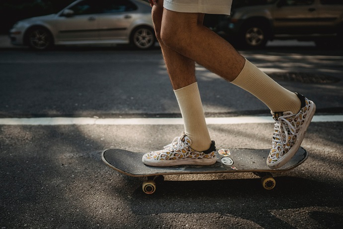 picture of a person on the street riding a skateboard with cool design sneakers and long socks