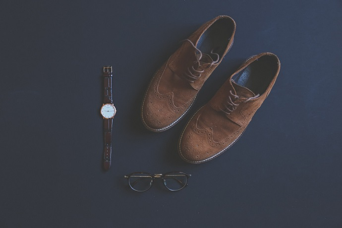 picture of comfortable men's shoes on a blue background beside a watch and pair of glasses