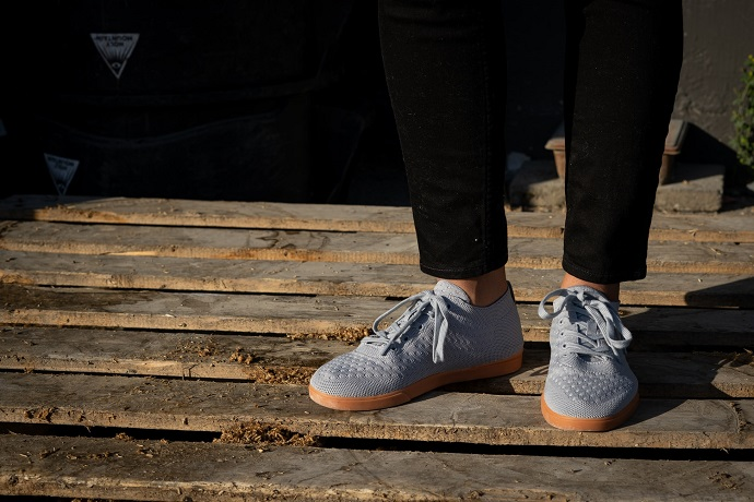 picture of a person standing on a wooden panel, wearing black jeans and blue sneakers