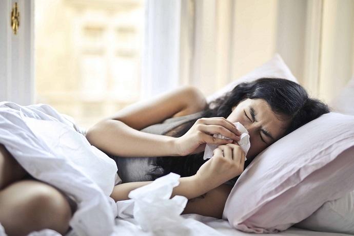 girl not feeling well lying on bed