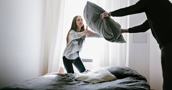 two people changing bed sheets