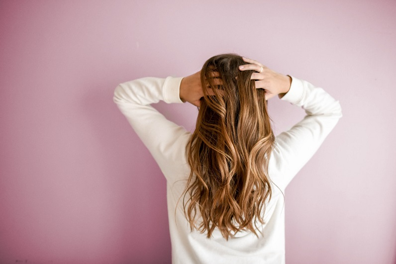 picture of a woman with hands in her hear in front a pink wall