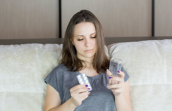 picture of a woman in bed holding pills and a glass of water