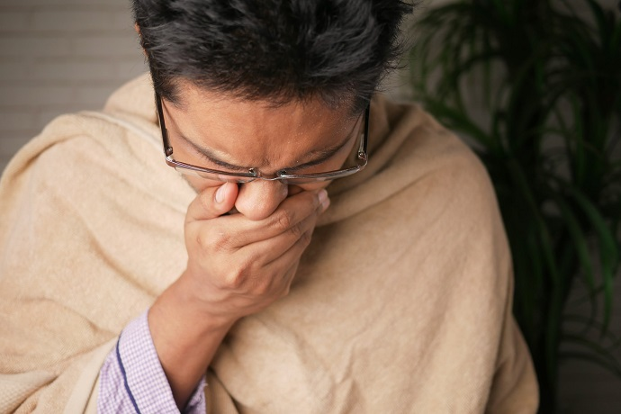picture of a man with a blanket sneezing in his hand