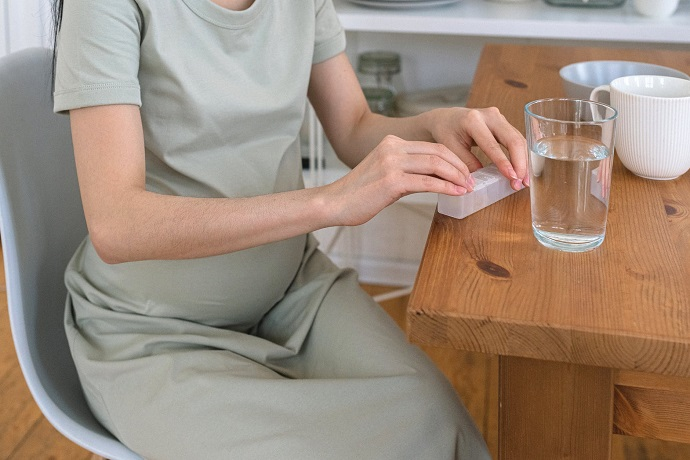 picture of pregnant woman taking pill with glass of water, sitting on a table